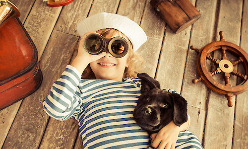 Child using binoculars hugging dog